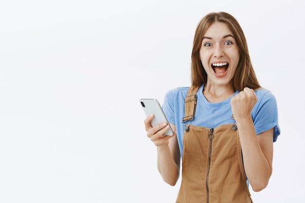 Opgewonden, verheugend mooi meisje dat reageert op geweldig nieuws online, smartphone vasthoudt en er gefascineerd uitziet