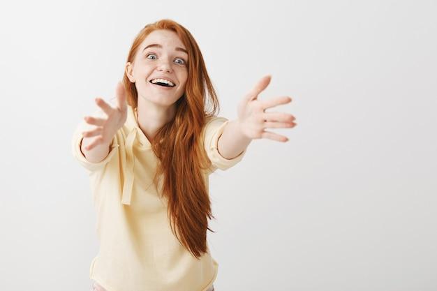 Opgewonden verleidelijk roodharig meisje glimlachend en handen naar voren reiken om iets vast te houden