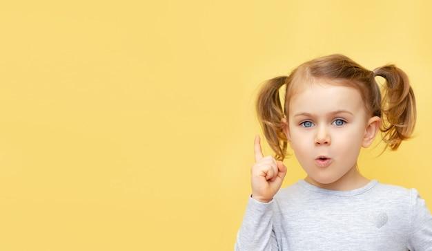 Opgewonden verrast kindmeisje dat camera bekijkt en vinger op exemplaarruimte richt die over gele muur wordt geïsoleerd