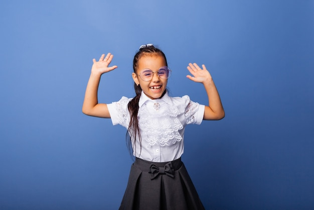 Opgewonden, verrast klein schoolmeisje glimlachend met het opsteken van de handen op een blauwe achtergrond geïsoleerde gele achtergrondkleur