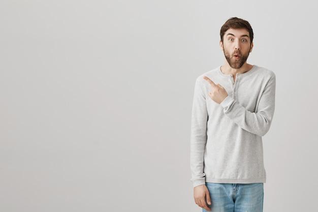 Opgewonden verrast man wijzende vinger naar links op advertentie