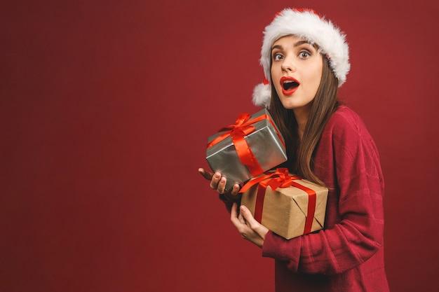 Opgewonden verrast vrouw in rode kerstman outfit bedrijf aanwezig