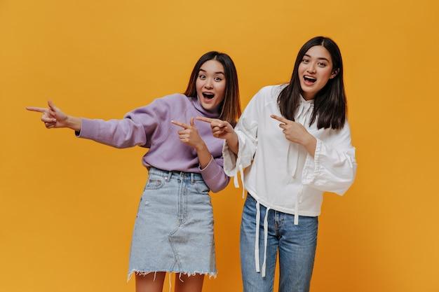 Opgewonden verraste aziatische vrouwen in denimoutfits en sweatshirts kijken naar voren en wijzen naar de plaats voor tekst op een geïsoleerde oranje muur