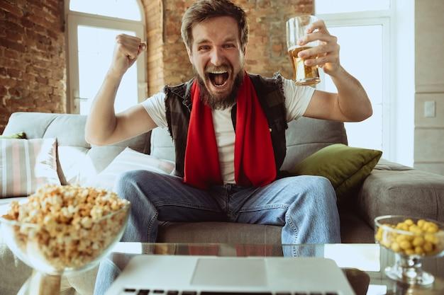 Opgewonden voetbalfan die thuis naar sportwedstrijden kijkt, ondersteuning op afstand van het favoriete team tijdens een pandemie van het coronavirus