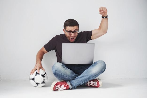 Opgewonden voetbalfan met een voetbal die op witte achtergrond wordt geïsoleerd. hij zit op de grond en kijkt op de laptop naar de resultaten van het spel en de beste momenten van de wedstrijd.