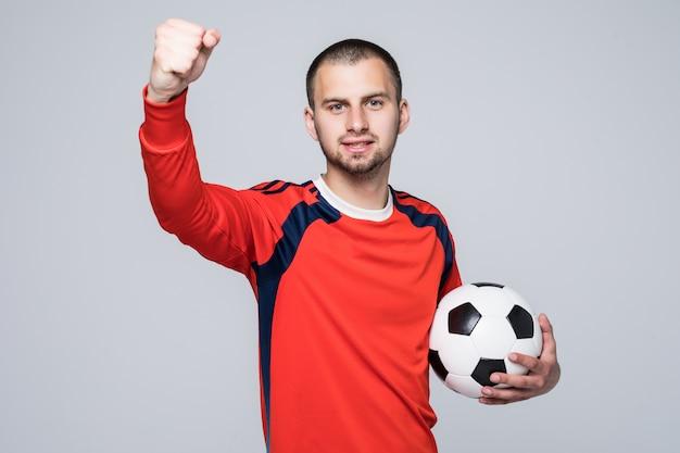 Opgewonden voetballer die in rood t-shirt een concept van de voetbaloverwinning houdt dat op wit wordt geïsoleerd