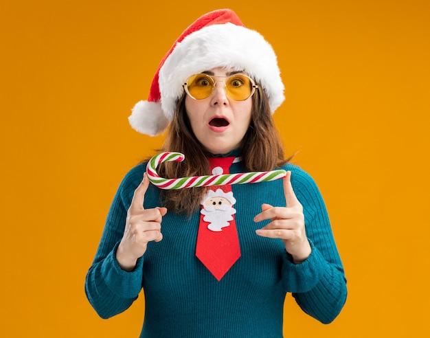 Opgewonden volwassen blanke vrouw in zonnebril met kerstmuts en santa stropdas met snoepgoed geïsoleerd op oranje muur met kopie ruimte
