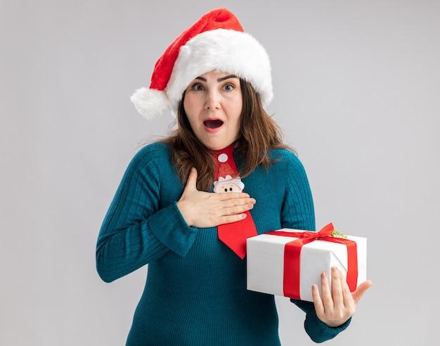 Opgewonden volwassen blanke vrouw met kerstmuts en stropdas santa legt hand op de borst en houdt kerst geschenkdoos geïsoleerd op een witte achtergrond met kopie ruimte