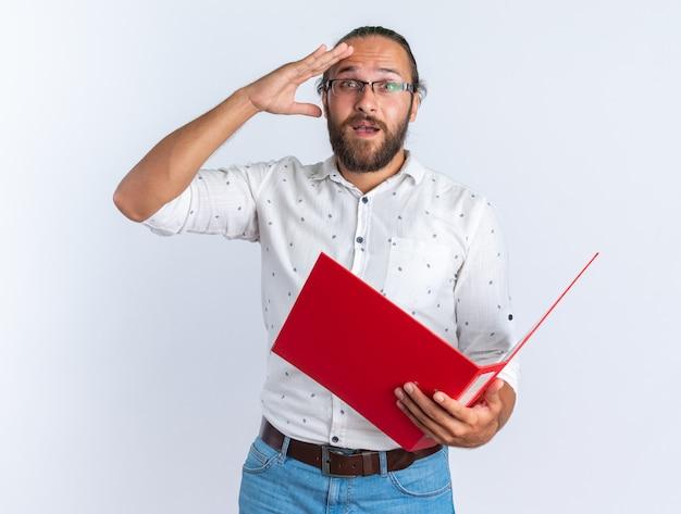 Opgewonden volwassen knappe man met een bril die een open map vasthoudt en de hand op het voorhoofd op afstand houdt