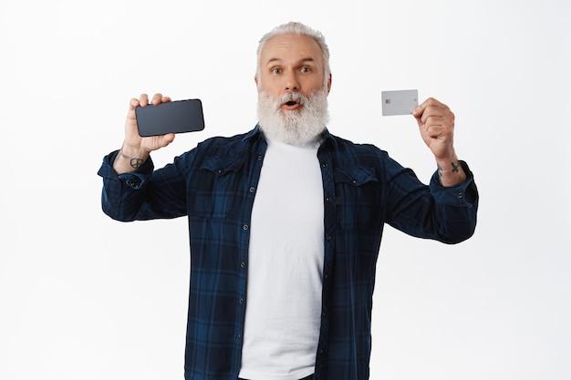 Opgewonden volwassen man die online winkel-app, contactloos betalen, witte muur aanbeveelt
