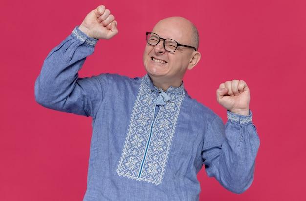 Opgewonden volwassen man in blauw shirt met een bril die zijn vuisten opheft