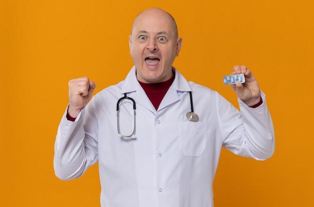 Opgewonden volwassen man in doktersuniform met stethoscoop die medicijnblisterverpakking vasthoudt en vuist omhoog houdt