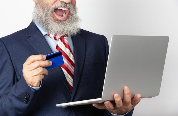 Opgewonden volwassen man in pak met een creditcard met behulp van online laptopaankoop. senior man met technologie op witte achtergrond.