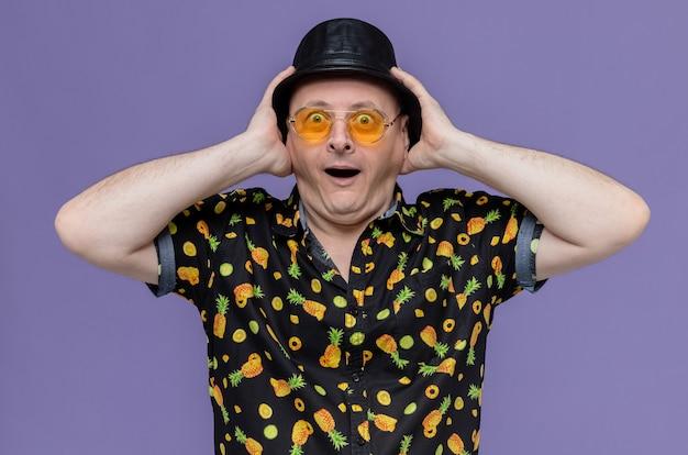 Opgewonden volwassen man met zwarte hoge hoed met een zonnebril die handen op zijn hoed zet en kijkt