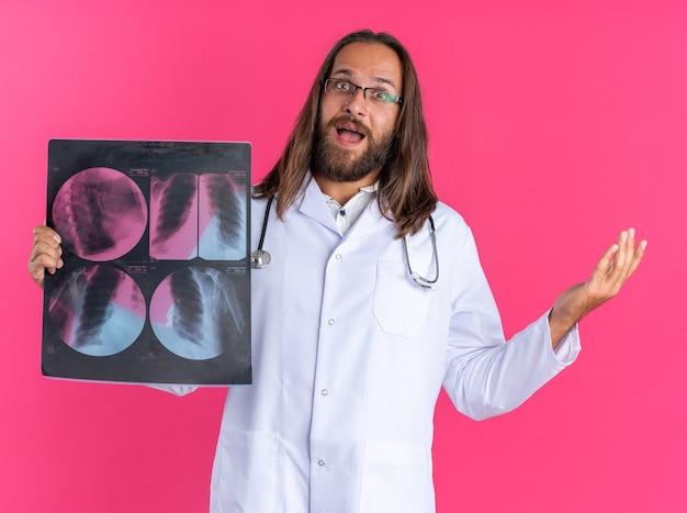 Opgewonden volwassen mannelijke arts met een medisch gewaad en een stethoscoop met een bril die naar de camera kijkt met een röntgenfoto en een lege hand die op een roze muur wordt geïsoleerd