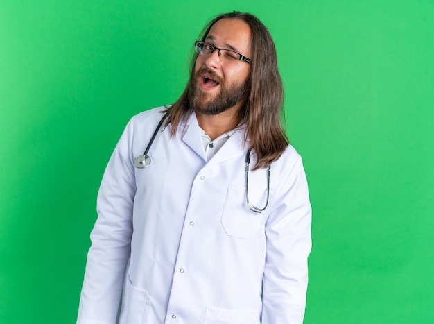 Opgewonden volwassen mannelijke arts met een medisch gewaad en een stethoscoop met een bril die naar een camera kijkt die knipoogt op een groene muur