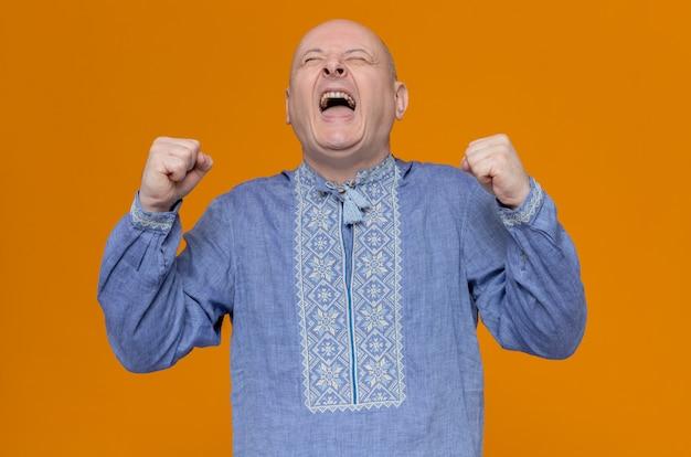 Opgewonden volwassen slavische man in blauw shirt met vuisten