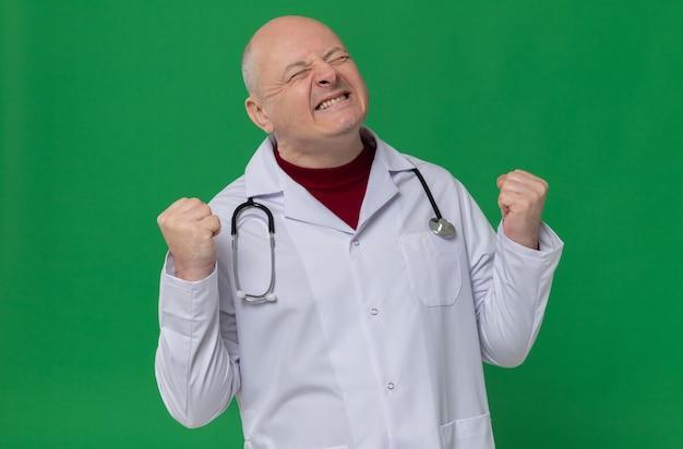 Opgewonden volwassen slavische man in doktersuniform met stethoscoop die vuisten omhoog houdt