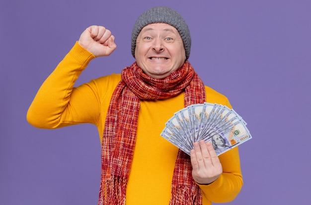 Opgewonden volwassen slavische man met wintermuts en sjaal om zijn nek die geld vasthoudt en vuist houdt