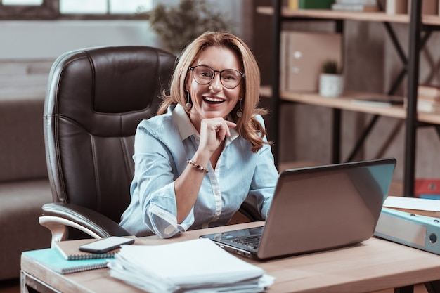 Opgewonden voor het werk. aangename ervaren advocaat die aan tafel zit en opgewonden voelt voor het werk