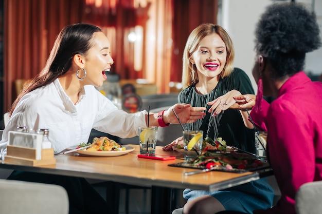 Opgewonden vrienden beste vrienden voelen zich opgewonden terwijl ze naar de verlovingsring van hun vriend kijken