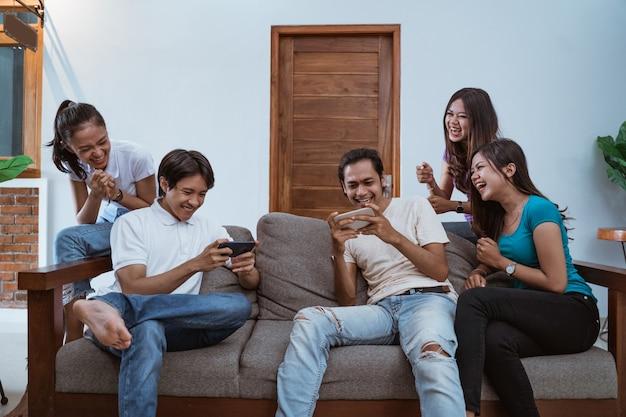 Opgewonden vrienden die samen games spelen met smartphones thuis, andere juichen op twee spelers
