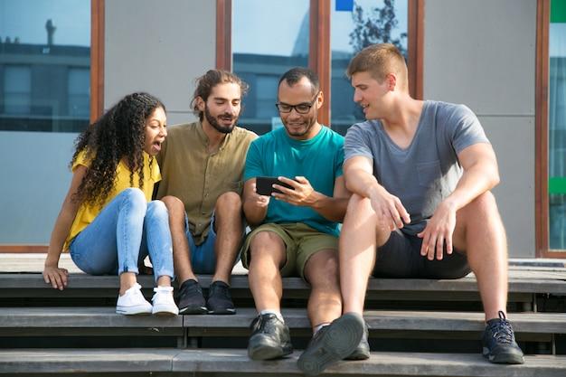 Opgewonden vrienden kijken naar video op mobiele telefoon