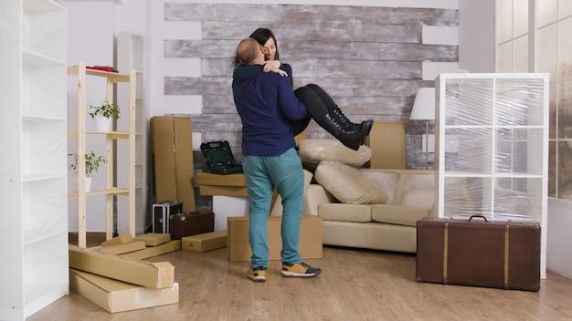 Opgewonden vriendje draait zijn vriendin in hun nieuwe appartement. vrolijk jong stel.
