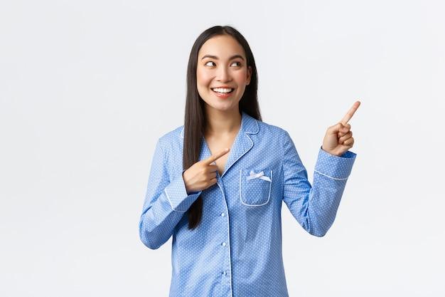 Opgewonden vrij aziatisch meisje in blauwe pyjama wijzende vingers in de rechterbovenhoek en kijken geïnteresseerd. blije vrouw in jammies die keuze maakt, met coole advertenties, witte achtergrond