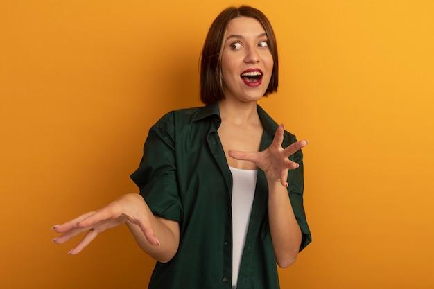 Opgewonden vrij blanke vrouw houdt handen open naar de zijkant op oranje te kijken