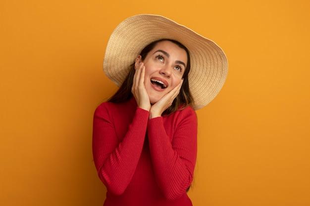 Opgewonden vrij blanke vrouw met strandhoed handen op gezicht en kijkt op oranje