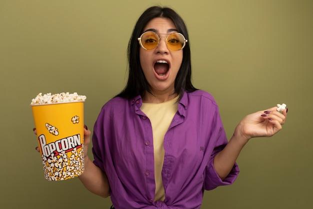 Opgewonden vrij donkerbruin kaukasisch meisje in zonnebril houdt popcornemmer op olijfgroen