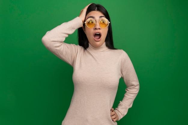 Opgewonden vrij donkerbruin kaukasisch meisje in zonnebril legt hand op hoofd en bekijkt kant op groen