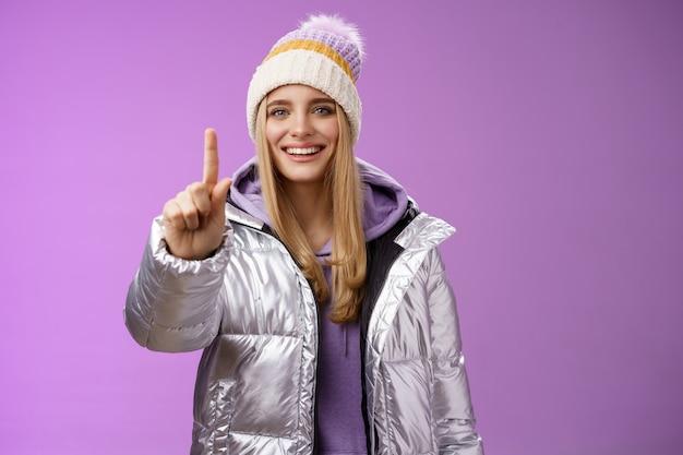 Opgewonden vrolijk blonde europees meisje in winter hoed zilver glanzend jasje toon nummer één wijsvingers geven suggestie advies breed glimlachend praten gelukkig, paarse achtergrond. kopieer ruimte