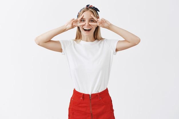 Opgewonden vrolijk jong blond meisje poseren tegen de witte muur