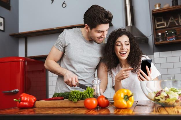 Opgewonden vrolijk jong stel dat gezonde salade kookt terwijl ze in de keuken zitten, kijkend naar mobiele telefoon