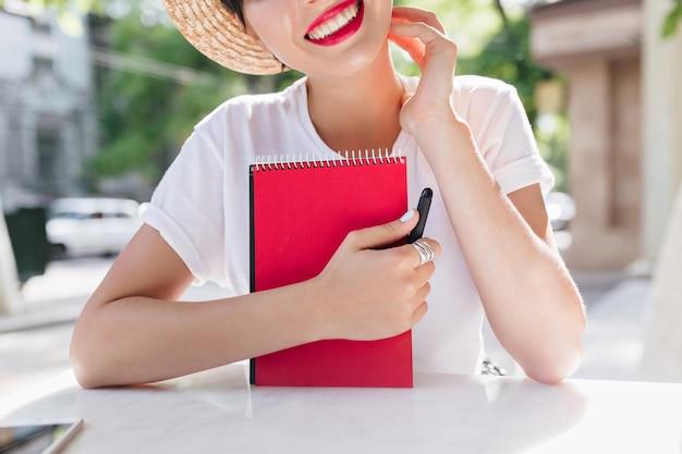 Opgewonden vrolijk meisje met rode planner boek koelen op terras in zomerochtend, poëzie creëren tijdens de lunch