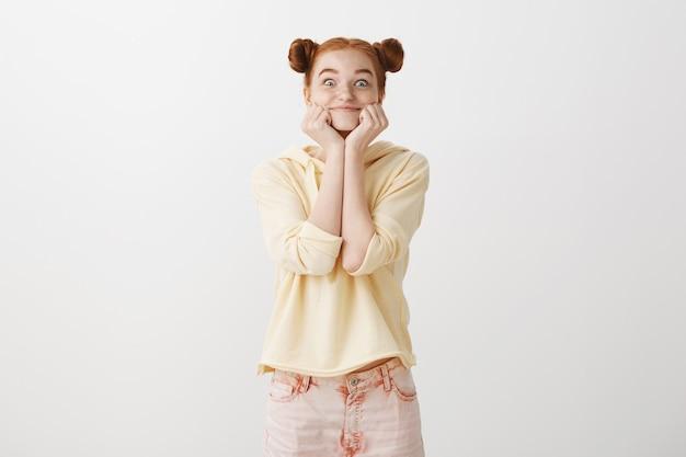 Opgewonden vrolijk roodharig meisje kijkt met verleiding en interesse