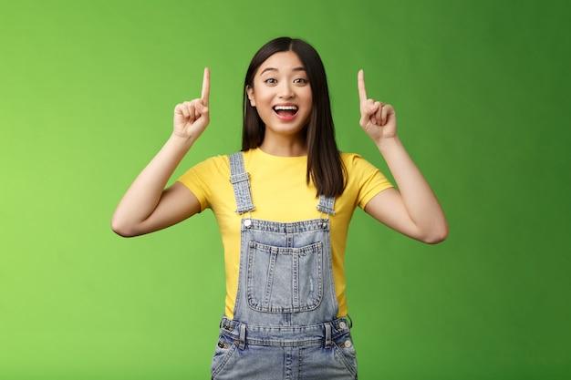 Opgewonden vrolijke aziatische brunette vrouw viert vreugdevol goed nieuws, wijst naar je geweldige informatie, glimlacht breed gefascineerd, bespreekt interessante promo en deelt graag advertenties.