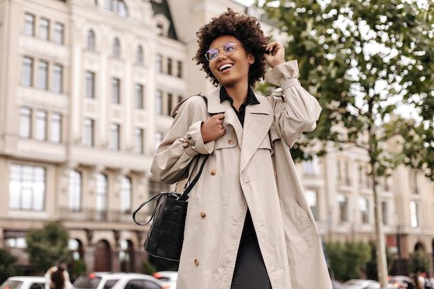 Opgewonden vrolijke brunette krullende vrouw in brillen, beige oversized trenchcoat glimlacht oprecht en loopt naar buiten