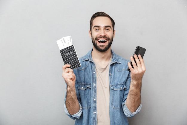 Opgewonden vrolijke man met shirt geïsoleerd over grijze muur, met paspoort met vliegtickets, met behulp van mobiele telefoon