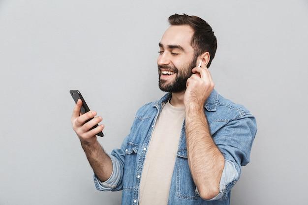 Opgewonden vrolijke man met shirt geïsoleerd over grijze muur, oortelefoons dragen, mobiele telefoon gebruiken, chatten