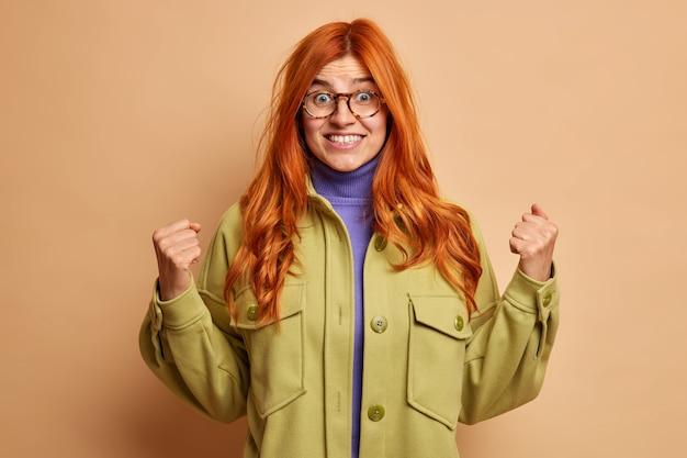 Opgewonden, vrolijke roodharige vrouw balde haar vuisten en lacht breed met vooruitziende blik om iets geweldigs gekleed in een groen jasje te horen.