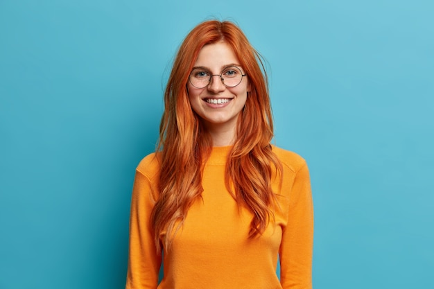 Opgewonden vrolijke roodharige vrouw met een oprechte brede glimlach heeft plezier en ziet er direct uit met een ronde optische bril gekleed in een oranje trui.