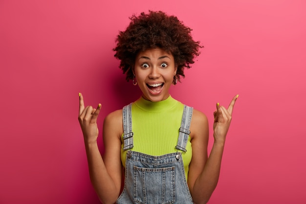 Opgewonden vrolijke vrouw, geboren om rockster te zijn, toont hoorn handgebaar, geniet van punkrockmuziek, blijft wild en vrij, is fan van heavy metal, gekleed in modieuze kleding, poseert binnen over roze muur