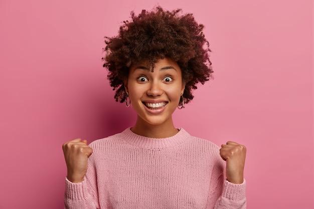 Opgewonden, vrolijke vrouw glimlacht breed, wacht op belangrijke resultaten, verheugt zich op positief nieuws, bereikt doel, ziet er vrolijk uit, draagt casual trui, poseert over roze muur, grijpt kans