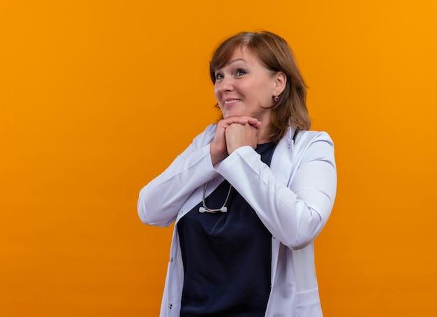 Opgewonden vrouw arts van middelbare leeftijd die medische mantel en stethoscoop draagt die handen op geïsoleerde oranje muur met exemplaarruimte samenbrengen
