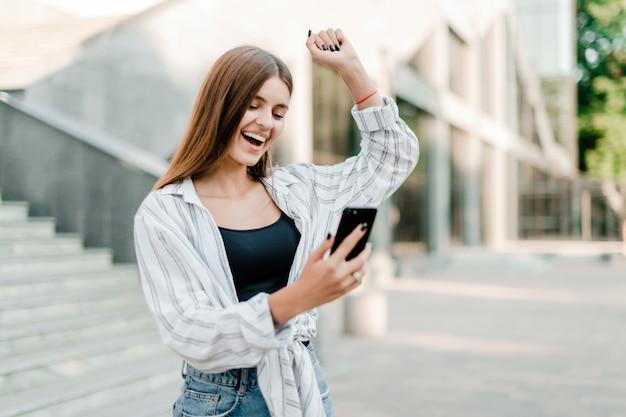 Opgewonden vrouw blij met haar overwinning aan de telefoon