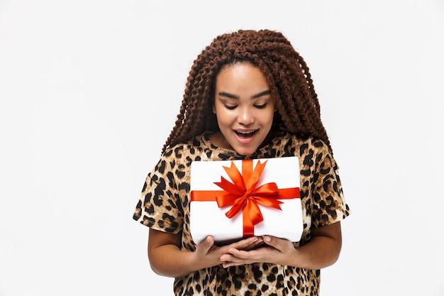 Opgewonden vrouw die lacht en de huidige doos met strik vasthoudt terwijl ze geïsoleerd tegen een witte muur staat