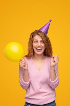 Opgewonden vrouw die met ballon verjaardag viert